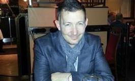 Steven Ellis sat at a tabl ein a pub with a beer
