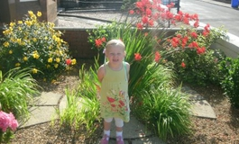 Freya in the garden surrounded by flowers