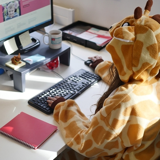 An employee in the office in a onesie as a way to fundraise at work
