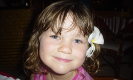 Chloe Pyne smiling with a flower in her hair