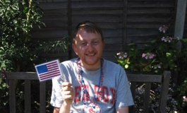 Keith Collins sat on a bench in the shade with an American flag