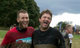 Supporters covered in mud taking part in Tough Mudder