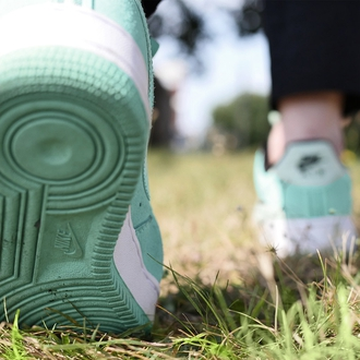 A close up of feet walking in trainers on the grass.