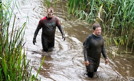 A supporter in the water taking part in Tough Mudder