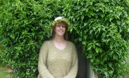 Sandy Wooley wearing a green jumper and skirt sat in the garden